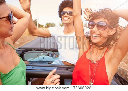Group Of Young Friends Dancing In Back Of Open Top Car