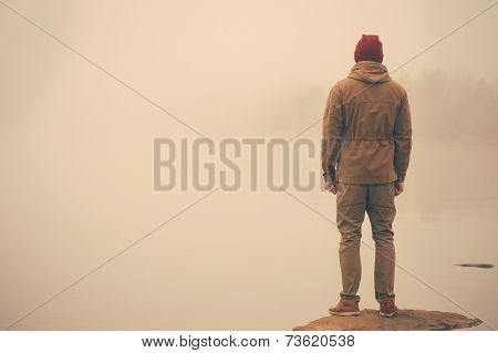 Young Man standing alone outdoor with foggy scandinavian nature on background Travel Lifestyle and melancholy emotions concept film effects colors poster