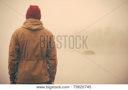 Young Man standing alone outdoor with foggy nature on background