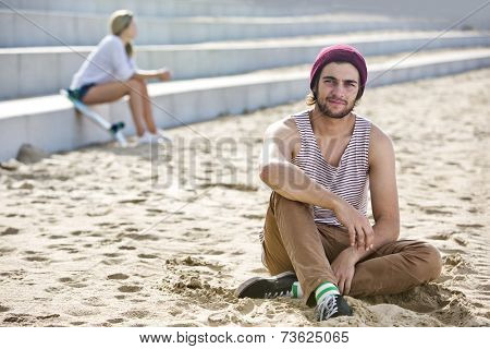 Profound looking dude, sitting in the sand on a beach with a woman sitting on concrete steps in the background.