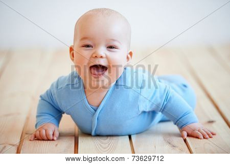 Cute happy baby boy crawling on the wooden deck or floor lifting itself up on its hands to laugh at the camera