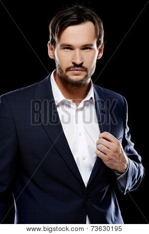 Handsome sexy stylish man in a smart jacket standing giving the camera a sultry seductive look  on a dark background