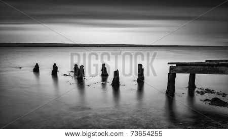 Long Exposure Landscape Of Old Derelict Jetty Extending Into Lake  Black And White