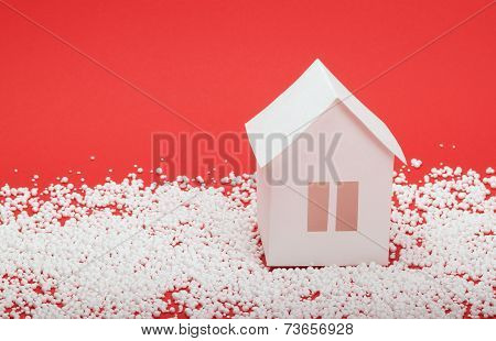paper house in snow on red background
