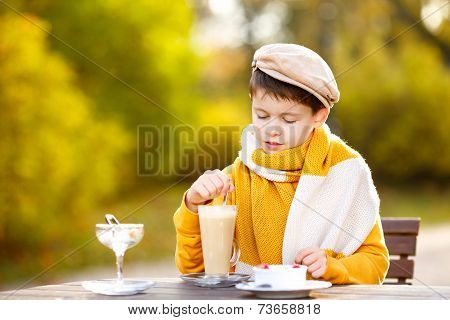 Little boy drinking hot chocolate in cafe