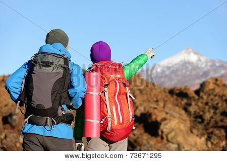 Hikers looking at view pointing hiking in mountain. People hiker couple in nature landscape trekking wearing backpacks. Woman and man on volcano Teide, Tenerife, Canary Islands, Spain