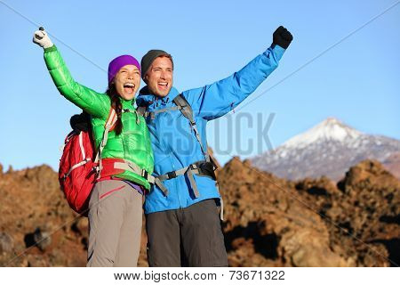 Happy celebrating winning hiking people at top. Cheering hiker couple enjoying freedom on hike with arms raised in mountain landscape. Woman and man on volcano Teide, Tenerife, Canary Islands, Spain