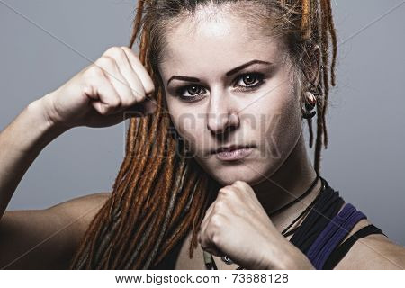 Close-up Portrait Young Woman With Dreadlocks In A Fighting Stance With His Fists