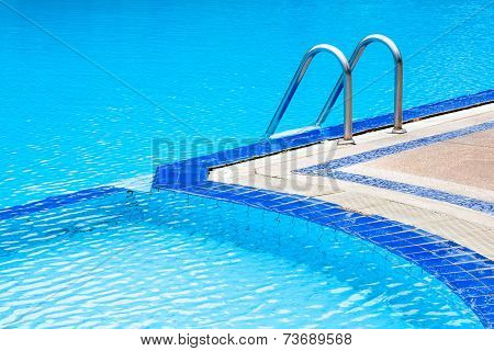 A View Of Curved Light Clear Blue Swimming Pool With Steel Ladder.