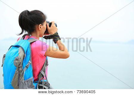 woman photographer taking photo seaside