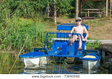 Smiling boy with glasses and a cap on a pedalo boat