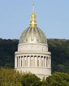 The golden West Virginia State Capital Dome towering above the trees on an clear early Fall evening just before sunset in Charleston WV. The building is made of limestone block and steel with real gold leaf applied to the copper and lead dome roof. poster