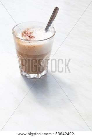 Foamy cappuchino in a coffee glass with spoon