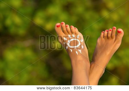 Woman's Foot With Sun-shaped Sun Cream In The Tropical Beach