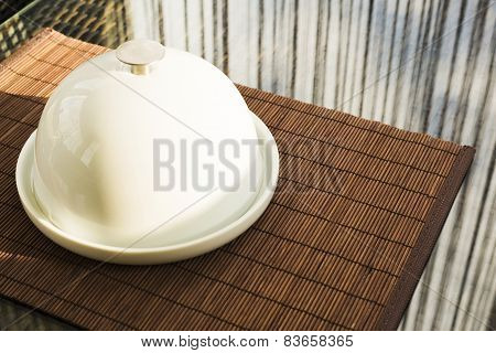 Ceramic salver with white dish over glass table