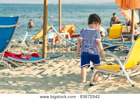 Toddler Dressed As A Sailor Standing Near A Beach Chair With Other People In Defocussed Background.