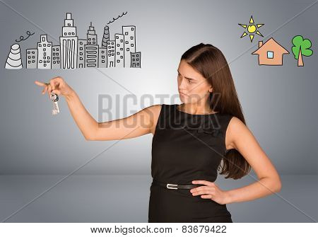 Woman making choice between city and country, looking at keys in her hand