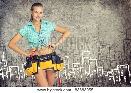 Woman in tool belt standing akimbo against stone wall with sketch of city on it