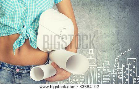 Woman holding hard hat and drawing rolls