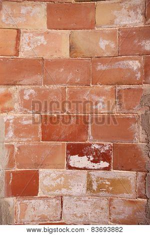 Detail of a semicircular rough brick wall