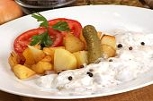 roasted potato with herring on a white plate poster