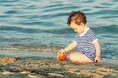 Toddler with sailor shirt sitting and playing at the edge of the waves on a beach. Photo with untraditional color rendering for artistic look poster