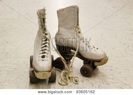 Old worn roller skates with big shoe-laces