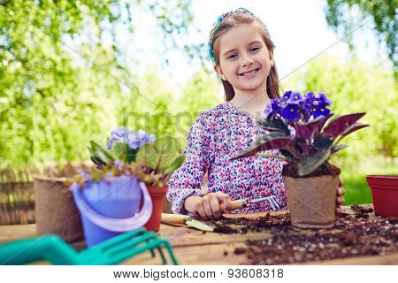 Cute little girl replanting African violets