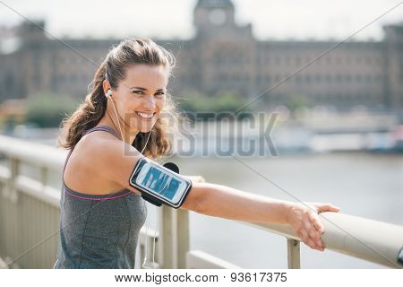 Smiling Woman In Workout Gear Listening To Music By City River