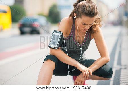 Woman Runner Kneeling, Looking Down, Listening To Music