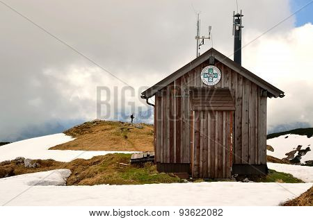 Hiker standing next to wooden hut in mountains.