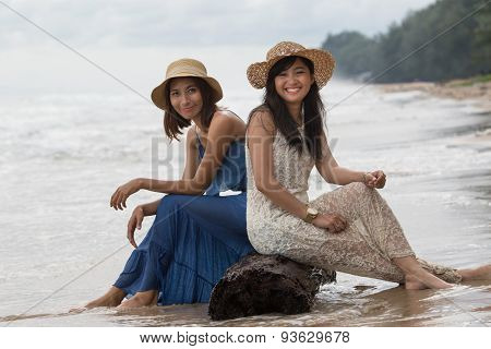 Portrait Of Young Beautiful Asian Tan Skin  Woman Wearing Fashion Straw Hat Sitting On Wood Lock At