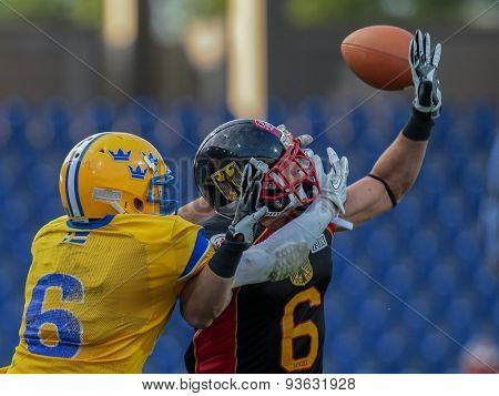 ST. POELTEN, AUSTRIA - JUNE 3, 2014: WR Fredrik Lsaksson (#6 Sweden) and DB Leonard Green (#6 Germany) fight for the ball during the Football EC European Championchip in St Poelten, Austria.