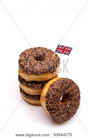 A stack of Chocolate donuts with a British Flag