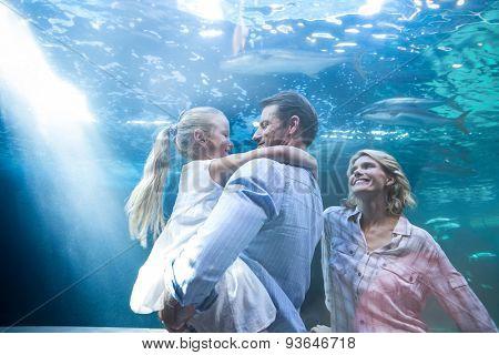 Happy family enjoying behing a fish tank at the aquarium