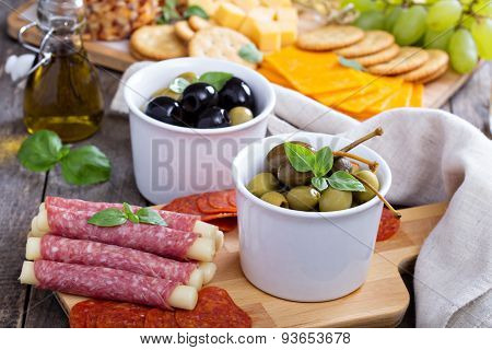 Variety of appetizers on dinner table salami, cheese, olives, capers, pepperoni poster