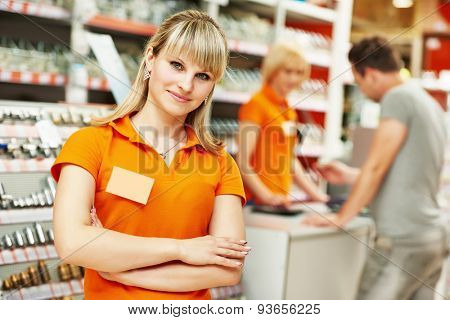 Positive female seller or shop assistant portrait  in hardware supermarket store