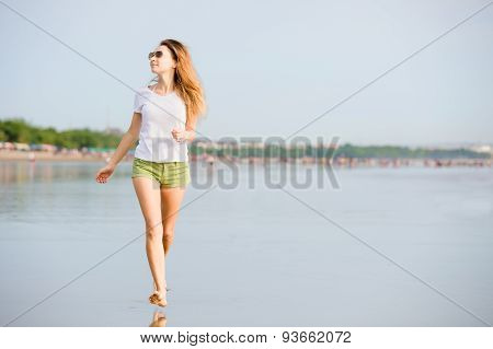 Young caucasion woman running on the beach at sunset