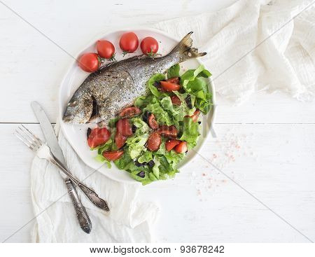 Cooked sea bream fish with fresh vegetable salad on ceramic plate over white rustic wooden backdrop,