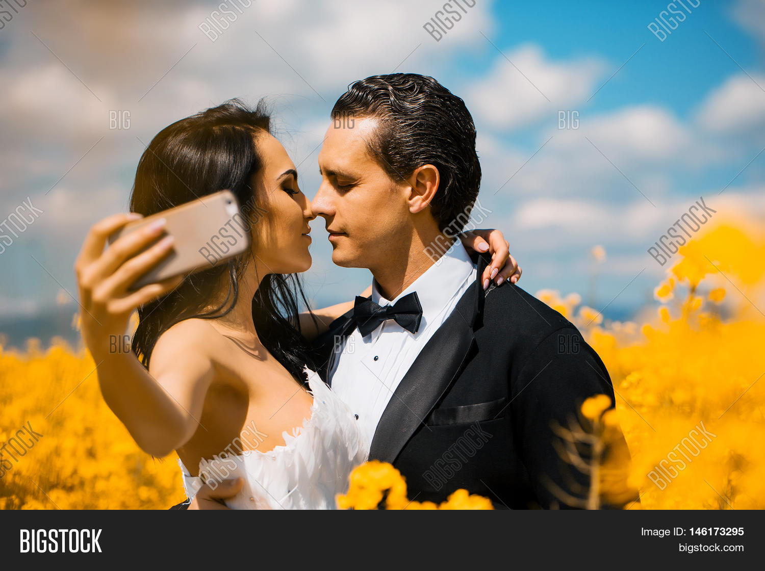 young wedding couple of sexy girl with pretty face in white bride dress  holds mobile phone and handsome man in black groom suit kiss in field with  yellow ... 4b3d17bea