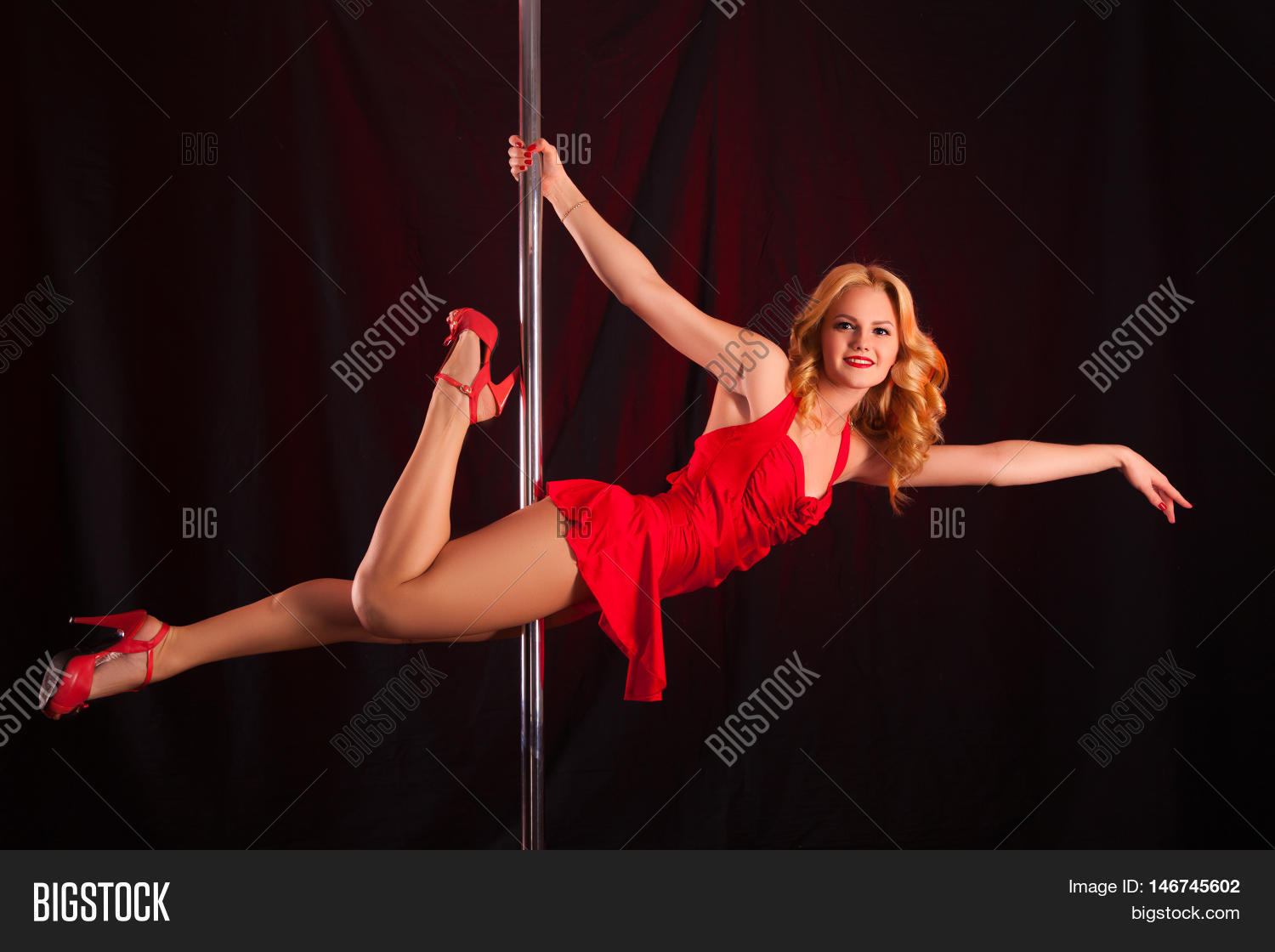 luxuriant sexy blonde in a red dress dancing on a pole. young girl on a