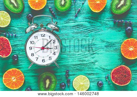 alarm clock - time to wake up with fruits on green wooden table, mock-up