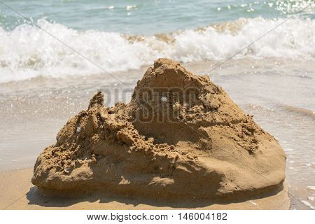 ephemeral sand castle on sandy beach in rough sea current