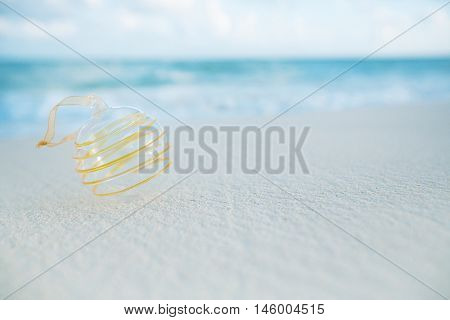 clear christmas glass ball on beach with seascape background