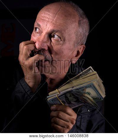 Sly Senior Man Holding Dollar Bills