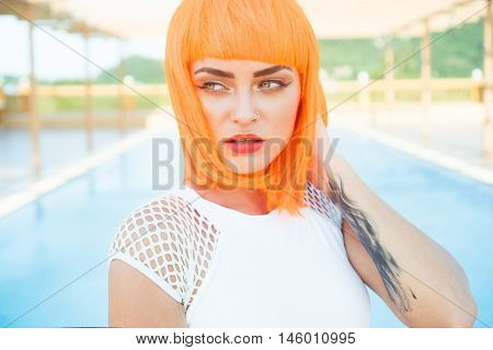 Closeup portrait of sexy beautiful woman in modern futuristic style posing by the rooftop pool during sunny summer day. Creative look of tattooed woman wearing white bikini and orange wig