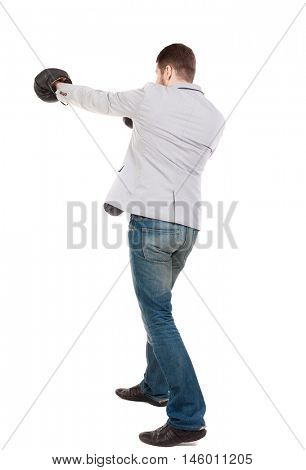 businessman with boxing gloves in fighting stance. guy in a gray jacket boxing gloves.