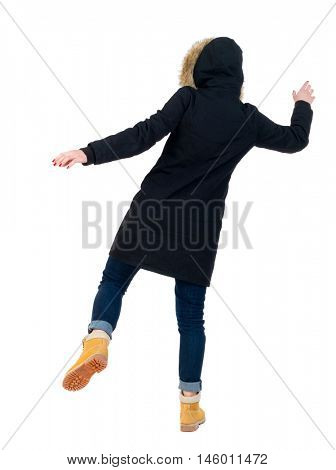 Back view woman in winter jacket Balances waving his arms. Standing young girl in parka. Girl in warm winter black jacket slipped and falls to the side.
