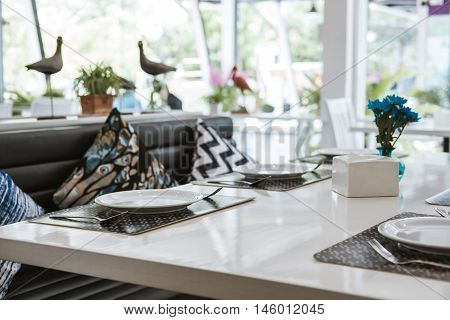 Modern white table in dining room with elegant table setting, selective focus, shallow depth of field