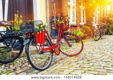 Retro vintage red bicycle on cobblestone street in the old town at sunrise.  Ribbe, Denmark